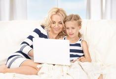 有膝上型计算机的愉快的母亲和子项 免版税库存图片