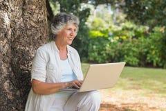 有膝上型计算机的愉快的灰发的妇女坐树 免版税库存图片