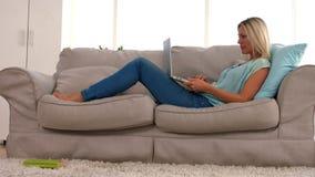 有膝上型计算机的愉快的金发碧眼的女人在沙发 股票视频