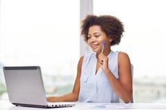 有膝上型计算机的愉快的非洲妇女在办公室 免版税库存照片