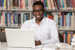 有膝上型计算机的愉快的非洲男学生在图书馆里 库存图片