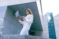 有膝上型计算机的成功的女孩在咖啡休息 库存照片