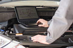 有膝上型计算机的技工诊断汽车 免版税库存图片