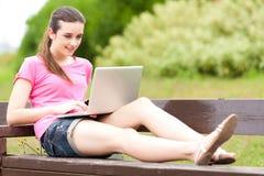 有膝上型计算机的新美丽的妇女 库存图片