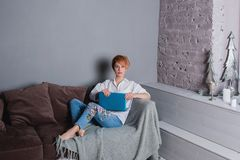 有膝上型计算机的时髦的少妇在沙发的手上和看照相机 穿戴在一件白色衬衣和牛仔裤有刺绣的 库存照片