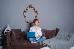 有膝上型计算机的时髦的少妇在沙发的手上和看照相机 穿戴在一件白色衬衣和牛仔裤有刺绣的 图库摄影