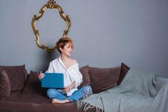 有膝上型计算机的时髦的少妇在沙发的手上和看照相机 穿戴在一件白色衬衣和牛仔裤有刺绣的 库存图片