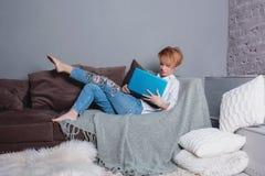 有膝上型计算机的时髦的少妇在沙发的手上和看膝上型计算机 穿戴在一件白色衬衣和牛仔裤有刺绣的 免版税库存图片