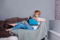 有膝上型计算机的时髦的少妇在沙发的手上和看膝上型计算机 穿戴在一件白色衬衣和牛仔裤有刺绣的 库存照片