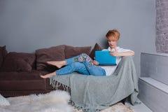 有膝上型计算机的时髦的少妇在沙发的手上和看膝上型计算机 穿戴在一件白色衬衣和牛仔裤有刺绣的 免版税库存照片