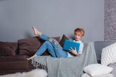 有膝上型计算机的时髦的少妇在沙发的手上和看膝上型计算机 穿戴在一件白色衬衣和牛仔裤有刺绣的 免版税图库摄影
