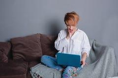 有膝上型计算机的时髦的惊奇的妇女在沙发的手上和看膝上型计算机 穿戴在一件白色衬衣和牛仔裤有刺绣的 免版税库存照片