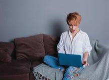 有膝上型计算机的时髦的惊奇的妇女在沙发的手上和看膝上型计算机 穿戴在一件白色衬衣和牛仔裤有刺绣的 免版税图库摄影