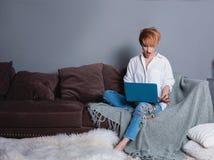 有膝上型计算机的时髦的惊奇的妇女在沙发的手上和看膝上型计算机 穿戴在一件白色衬衣和牛仔裤有刺绣的 库存照片
