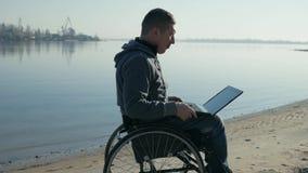 有膝上型计算机的残疾人,在轮椅主角录影闲谈,单独 影视素材