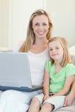 有膝上型计算机的母亲和女儿在沙发 库存图片