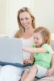 有膝上型计算机的母亲和女儿在长沙发 免版税库存图片