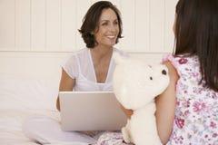 有膝上型计算机的母亲在床上的看女儿 免版税库存照片