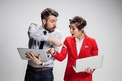 有膝上型计算机的沟通在灰色背景的年轻商人和女实业家 库存图片