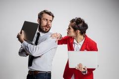 有膝上型计算机的沟通在灰色背景的年轻商人和女实业家 库存照片