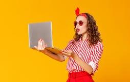 有膝上型计算机的滑稽的快乐的妇女在黄色背景 库存图片