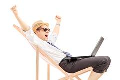 有膝上型计算机的激动的人坐海滩睡椅 免版税图库摄影