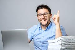 有膝上型计算机的激动的年轻人指向手指的  免版税库存照片