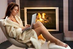 有膝上型计算机的热妇女在壁炉前面 库存图片