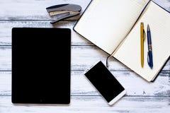 有膝上型计算机的现代工作场所、金黄和银色笔、智能手机、笔记薄和订书机 库存图片