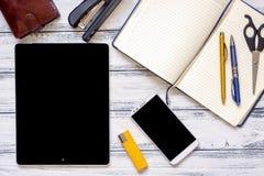 有膝上型计算机的现代工作场所、金黄和银色笔、智能手机、皮革钱包、剪刀、打火机、笔记薄和订书机在白色w 免版税库存图片