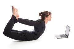 有膝上型计算机的瑜伽妇女 免版税库存图片