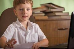有膝上型计算机的男孩在桌上 库存照片