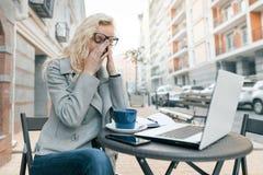 有膝上型计算机的疲倦的女商人在室外咖啡馆,接触她的与她的玻璃的妇女眼睛,城市街道背景 库存照片