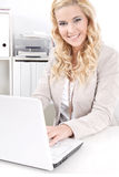 有膝上型计算机的白肤金发的女商人 库存图片