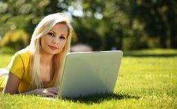 有膝上型计算机的白肤金发的女孩 微笑的美丽的妇女 库存图片