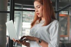 有膝上型计算机的确信的年轻亚裔女实业家有想法在办公室 认为和周道的企业概念 免版税库存图片