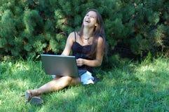 有膝上型计算机的笑的女孩 库存图片