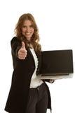 有膝上型计算机的美丽的女实业家显示赞许 免版税库存图片