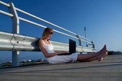 有膝上型计算机的美丽的妇女在度假 库存照片