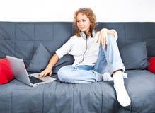 有膝上型计算机的美丽的妇女在男朋友的牛仔裤 图库摄影