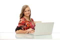 有膝上型计算机的美丽的微笑的妇女 免版税库存照片