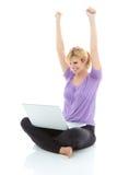有膝上型计算机的美丽的白肤金发的女性在网上赢取某事的 库存图片