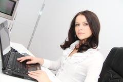 有膝上型计算机的美丽的年轻女商人在办公室 免版税库存图片