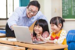 有膝上型计算机的老师教的孩子 免版税库存照片