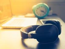 有膝上型计算机的耳机在办公桌和阳光上在下午 库存图片