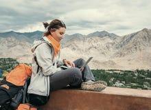 有膝上型计算机的背包徒步旅行者坐顶视图点在山下 免版税库存照片