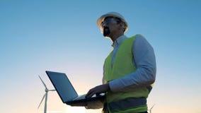 有膝上型计算机的能学专家和在他附近的风车工作 替代背景概念数字式能源例证太阳风 股票录像