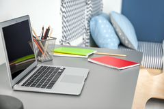 有膝上型计算机的舒适的工作场所在书桌上 库存照片