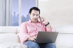 有膝上型计算机的英俊的人在公寓 免版税图库摄影