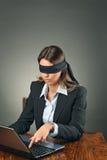 有膝上型计算机的蒙住眼睛的女商人 免版税库存图片